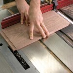 A fair amount of downward pressure ensures accuracy with this technique. If you don't keep the board pressed down flat, it will try to rise up on you. Even a bit of this will result in a too-thick tenon. If you are not sure that you are holding the piece down firmly, make a second pass over the blades.