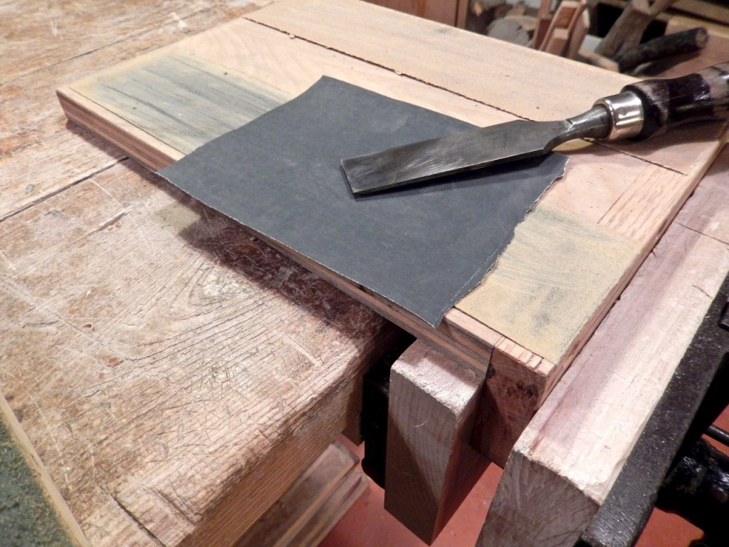 I place a 400 or 600 grit sandpaper over the 180 grit strip to break the burr (in the case of a chisel) and for the initial honing process on the bevel.