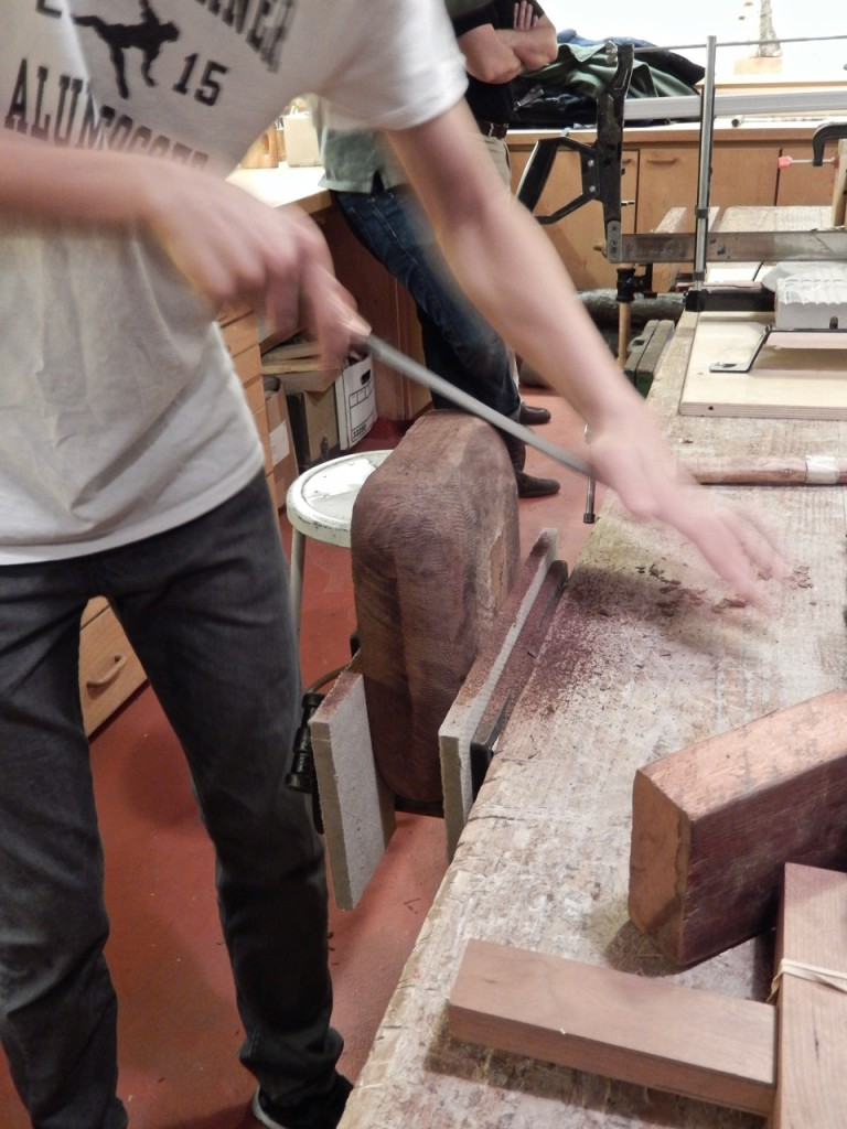 One of our 10th graders demonstrate carving a wooden bowl. In this image he rasp the bowl exterior.