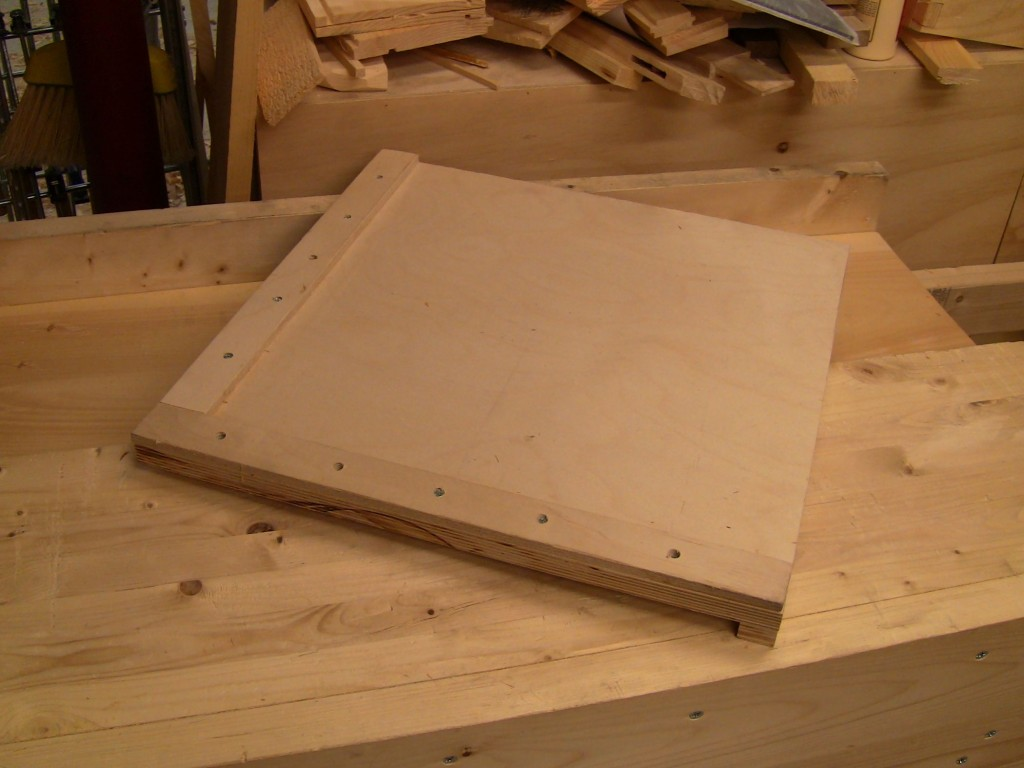 A square planing board, bench hook style.