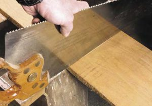 When I rotate the saw a bit, the reflection lines up with the board. The saw is square across the width. Now I simply draw a pencil line along the back of the saw and I have my cut line.