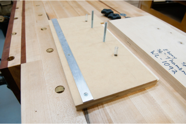 The aluminum bar makes a pivot point for the top of the jig to clamp down on the Ebony blank.